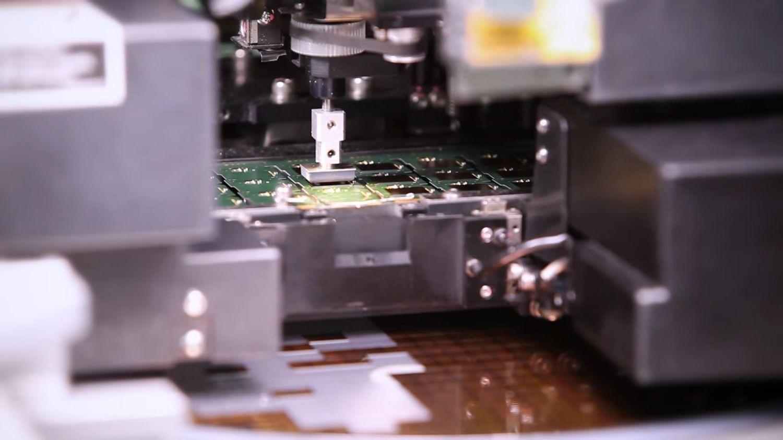 Una máquina recoge un chip de un alimentador y lo coloca en la PCB