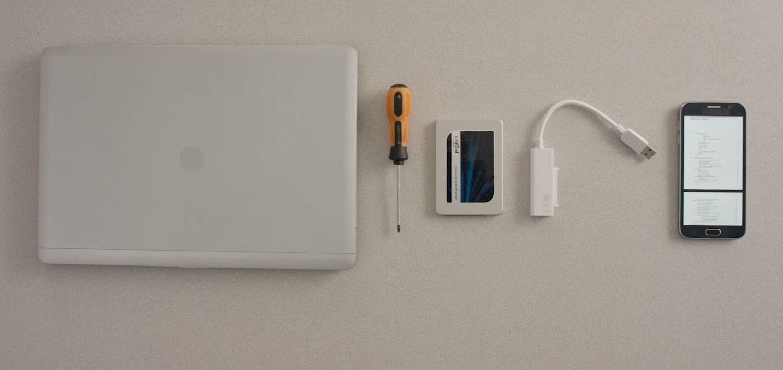 Un portátil, una SSD Crucial, un destornillador y el manual de usuario de un ordenador, mostrado en un móvil, descansan sobre la superficie de un escritorio