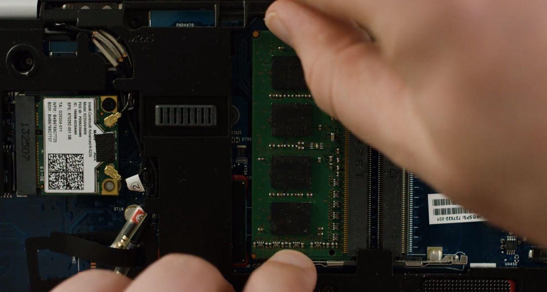 Una persona retirando un módulo de memoria RAM del interior de un ordenador portátil
