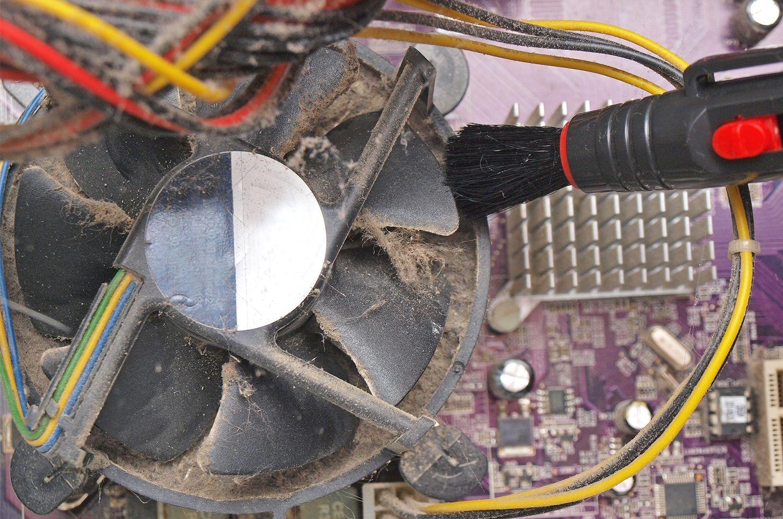 Un pequeño cepillo limpia el polvo y las pelusas de un ventilador extraído de un ordenador de sobremesa