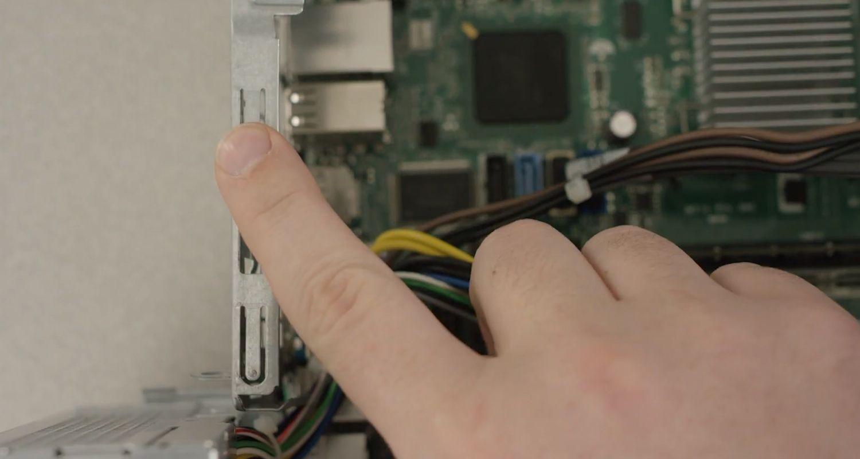 El dedo de una persona tocando una de las superficies metálicas sin pintar de un ordenador para descargar la electricidad estática