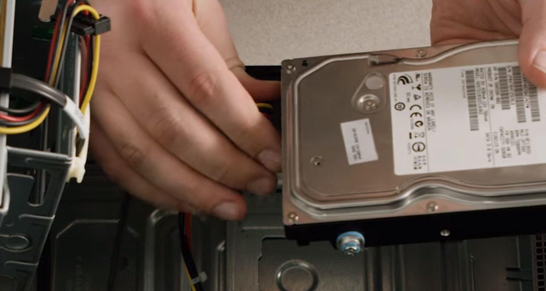 Una persona desconecta los cables de la unidad de almacenamiento de un ordenador de sobremesa