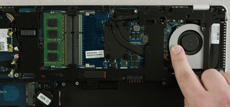 El dedo de una persona toca una superficie metálica sin pintar en la parte inferior expuesta de un ordenador portátil para descargar la electricidad estática.
